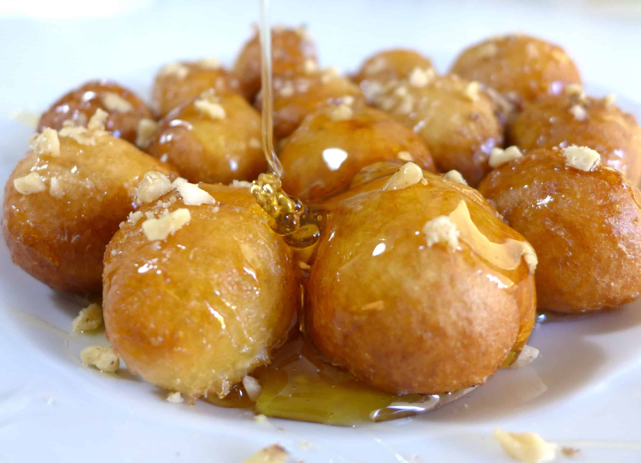Greek donuts (Loukoumades) drizzled with honey and walnuts